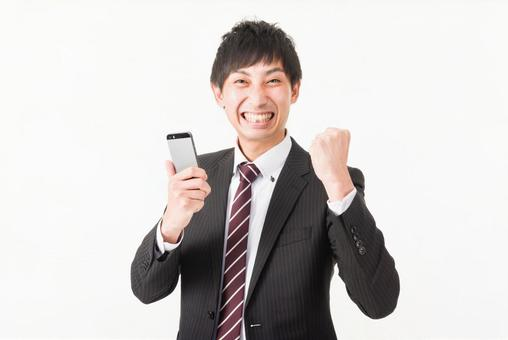 A businessman who carries a guts pose with a mobile phone