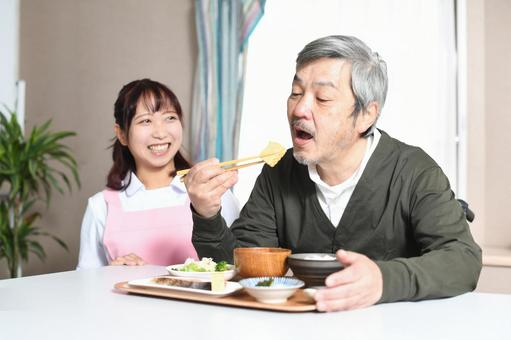 Elderly man eating and a female caregiver in an apron