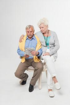 Foreigner senior couple sitting in a chair and reading newspaper 1