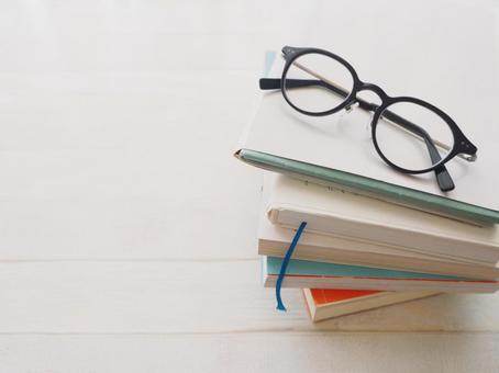 Books and glasses reading autumn wood grain background