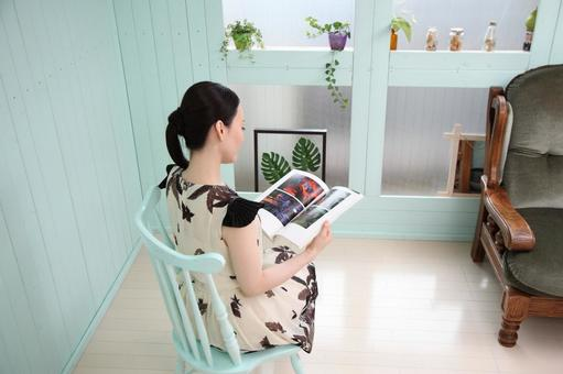 A woman sitting in a chair and reading a book
