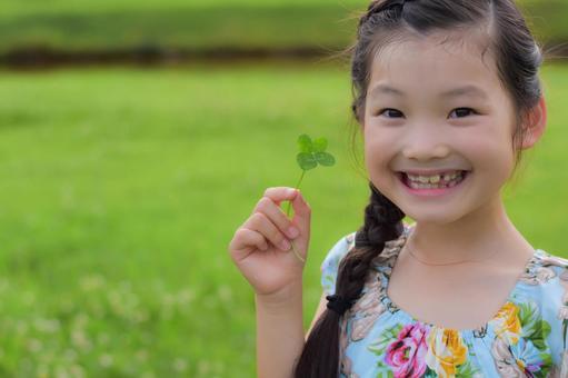 四つ葉のクローバーを持つ子供