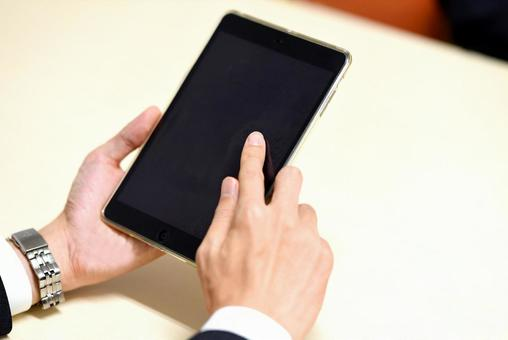 Hands of a businessman operating a tablet