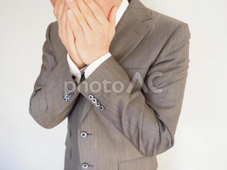 ビジネスマン【手で口をおさえる男性】の写真