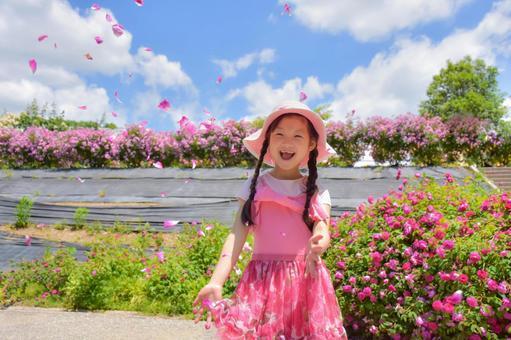 有玫瑰花瓣和微笑的一個女孩