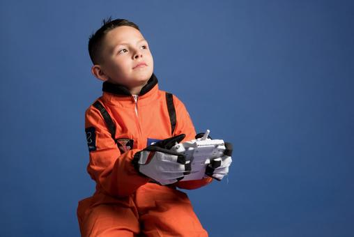 Boy 2 wearing a space suit and holding a controller