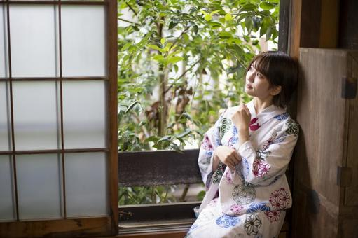 Yukata woman sitting by the window and looking at the outside scenery
