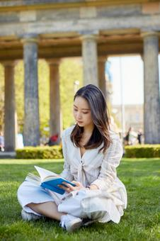 Asian woman reading a book on the lawn 3