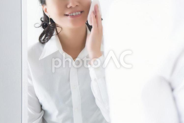 メイクする女性(笑顔)の写真