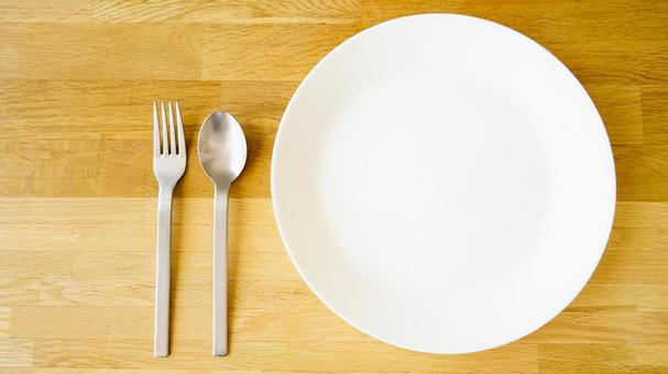 Meal image with a white plate, fork and spoon on a wood grain table