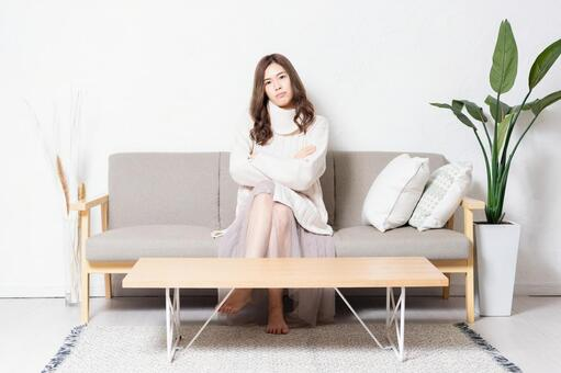 A young woman sitting on the sofa in the living room and thinking