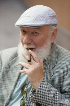 A foreign elderly man who smokes a cigar 1