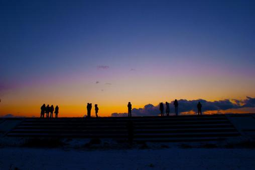 People on breakwater and morning glow