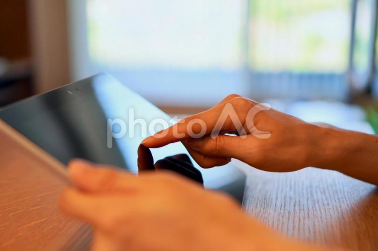 タブレットを操作する女性の手の写真