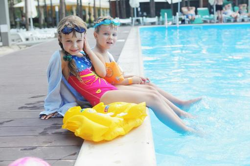 A girl and a boy sitting on the edge of the pool 1