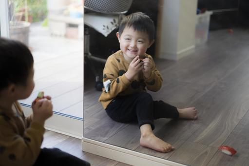 3-year-old child laughing in the mirror