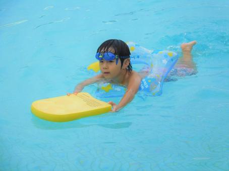 Children swimming on a pool kickboard