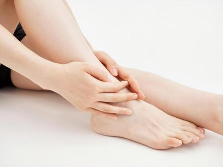 A woman holding a painful leg joint on a white background