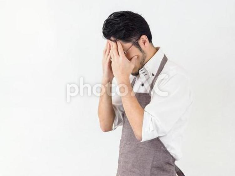 家事に失敗・反省・困惑している男性のイメージの写真