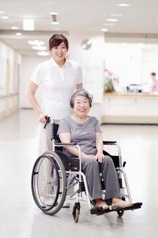 屋内で車椅子に乗っているおばあちゃんと介護士1