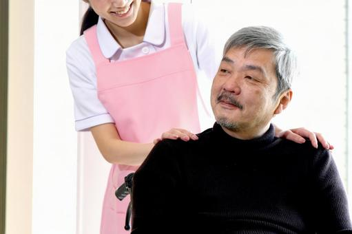 A young caregiver woman in an apron talking to a senior man in a wheelchair