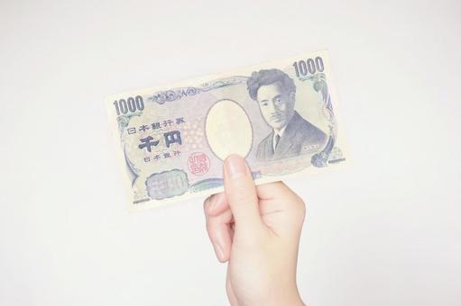 Hand holding a 1000 yen bill (center)