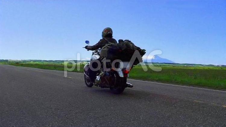北海道の道を駆けるバイクの写真