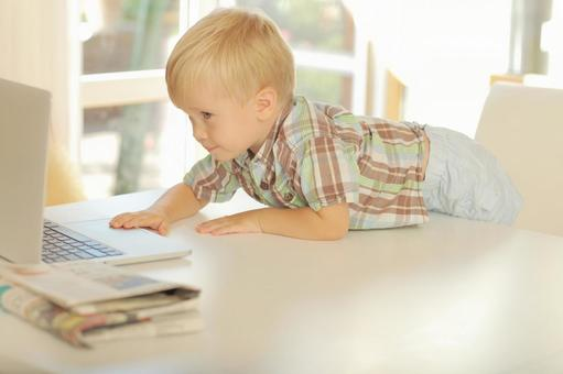 A little boy who embarks on a white desk and looks at the computer 1