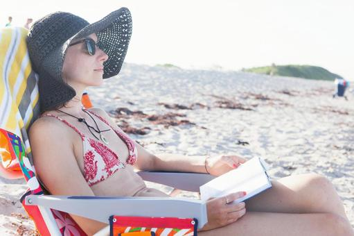 Female 2 sitting on a beach chair to read
