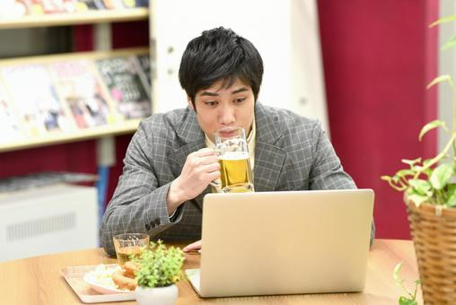 A man drinking alcohol while looking at a PC