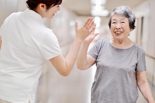 ハイタッチするおばあちゃんと介護士2