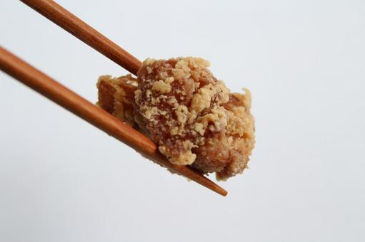 Fried chicken with chopsticks on a white background