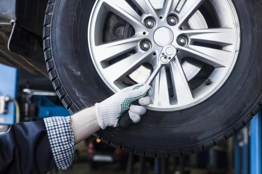 Automobile mechanic servicing tires 2