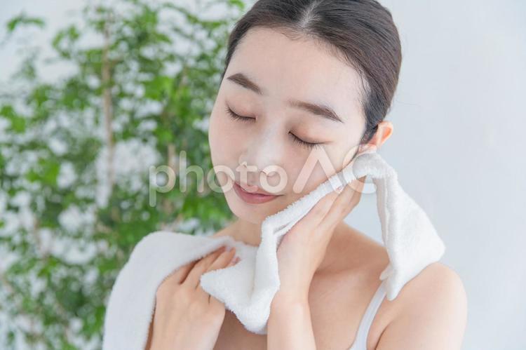 タオルで顔をふく女性の写真