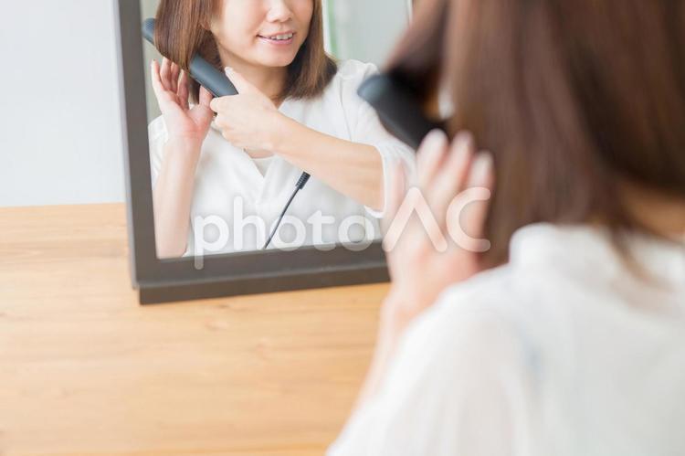 ヘアアイロンを使う女性(笑顔)の写真