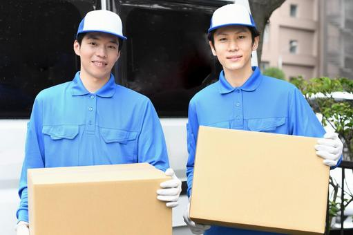Image of multiple men wearing work clothes carrying moving cardboard in front of a car