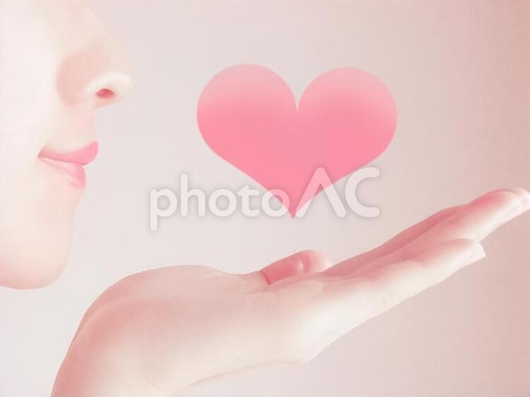 ハートを見つめる女性の写真