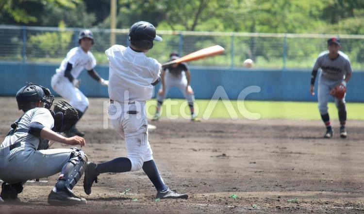 高校野球・得点のチャンスにシュアなバッティングで三塁線を抜く強い当たりを打つ強打の右バッターの写真