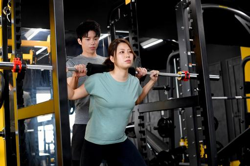 Asian women carrying barbells and male trainers assisting