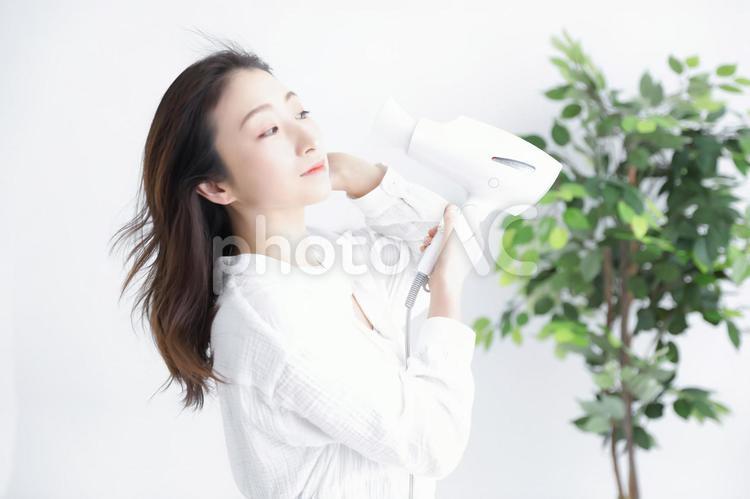ドライヤーを使う女性の写真