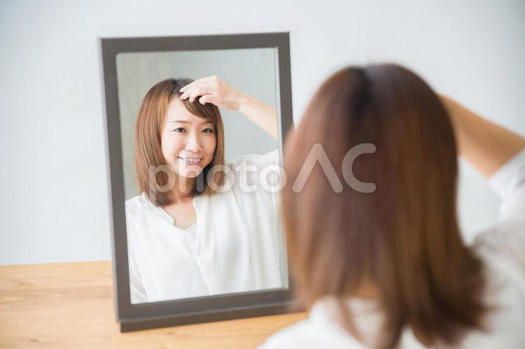 前髪を気にする女性(笑顔)の写真