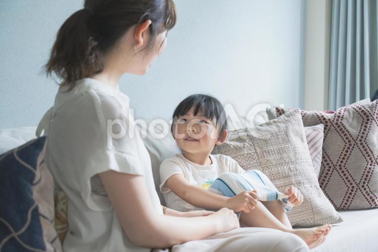 ソフェのうえで会話する親子の写真
