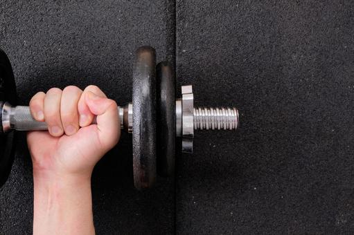 Hands lifting the dumbbells on the rubber mat