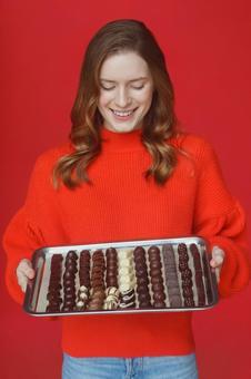 トレーに並んだチョコレートを持つ笑顔の女性