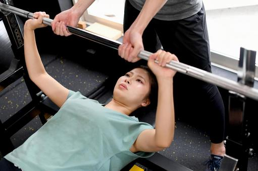 Asian women doing bench press (muscle training) and male trainers assisting