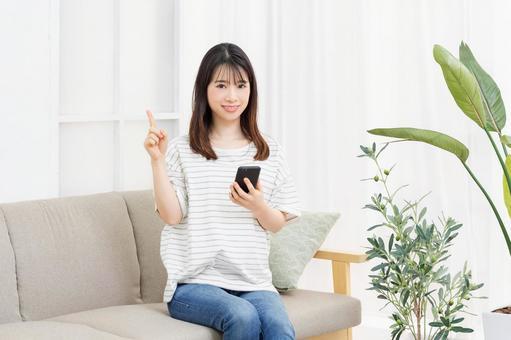 一個年輕女子坐在房間裡的沙發上,操作她的智能手機
