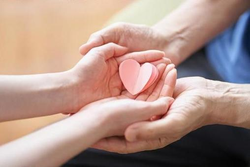 Hands of caregivers and elderly people with heart-shaped objects