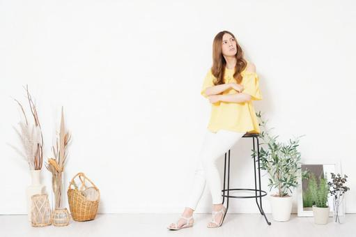 A young woman sitting in a chair in front of a white wall and thinking