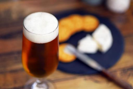 Beer, Camembert cheese and crackers poured into a glass