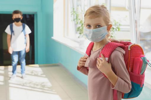 小學生戴著口罩,站在走廊上
